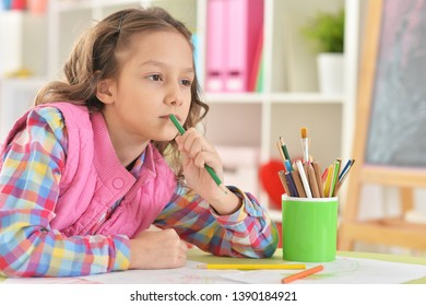 Portrait of girl sitting at table and drawing