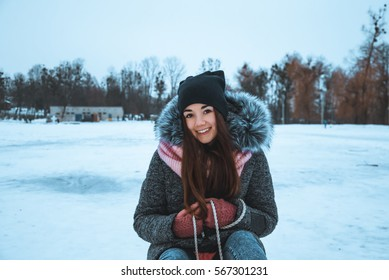 Portrait of a girl with sled in winter