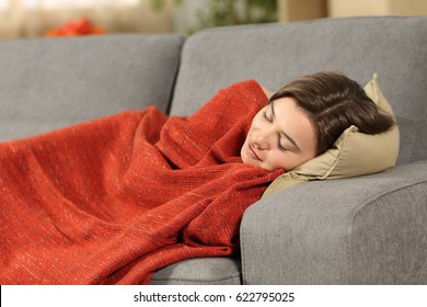 Portrait of a girl sleeping covered with an orange blanket lying on a comfortable couch in the living room at home