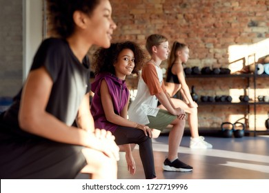 Portrait of a girl smiling at camera while warming up, exercising together with other kids in gym. Sport, healthy lifestyle, physical education concept. Horizontal shot. Selective focus