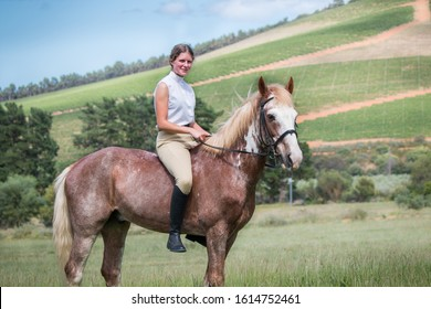 Portrait of a Girl smiling and sitting on her Sabino paint horse in the field both facing the camera side view.