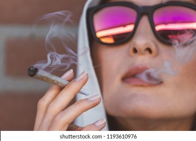 Portrait of a girl smoking marijuana joint on the street of Amsterdam (Holland - Netherlands) - medical marijuana use and legalization of cannabis, pregnant woman dangerous smoking concept