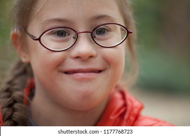 Portrait of a girl with special needs in glasses close-up in nature