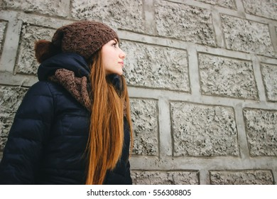 portrait of a girl in the spring in the concrete cement wall of a building in the city