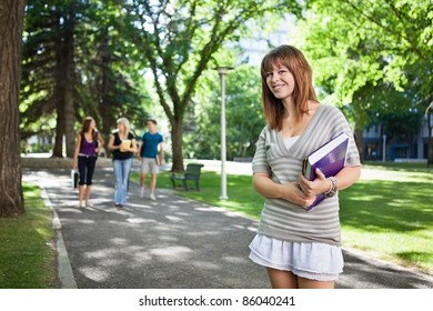 Portrait of girl standing with a book while her friends walking in background