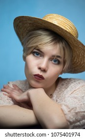 Portrait of girl in straw hat on blue background