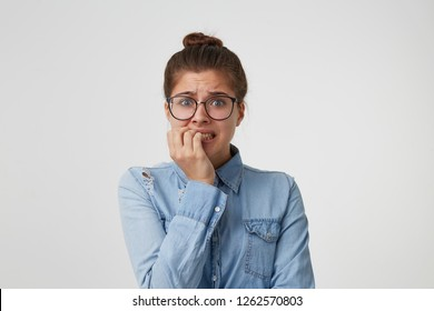 Portrait of a girl student in glasses, dressed in a fashionable denim shirt, worries about something, nervous,bites her nails, waiting for the exam results isolated on white background
