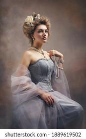 Portrait of a girl styled like an antic princess or countess dress like a paint