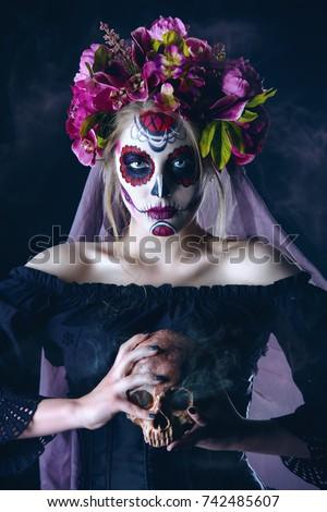 Portrait of a girl with sugar skull makeup over black background. Calavera Catrina. Dia