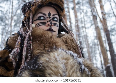 Portrait of a girl in the suit of a wild hunter from animal fur, from a perspective from the bottom up against a winter forest covered with snow