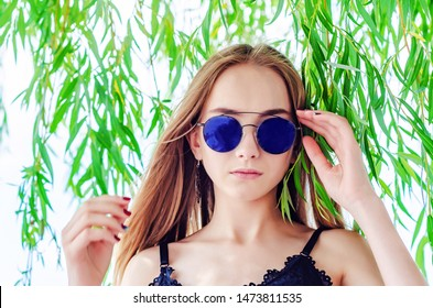 Portrait of a girl in sunglasses on a background of green willow branches. Beauty, youth.