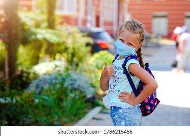 Portrait of a girl in a surgical mask showing a thumb up gesture. Concept of coronavirus COVID-19. Schoolgirl wearing medical face mask to health protection from influenza virus. Back to school .