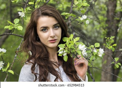 Portrait of a girl surrounded by white blossoming apple trees