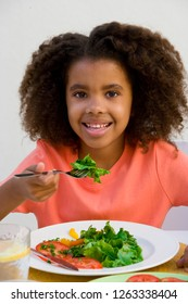 Portrait of girl at table eating fresh healthy salad