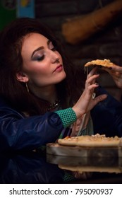 portrait of girl taking bite of  piece of pizza in cafe