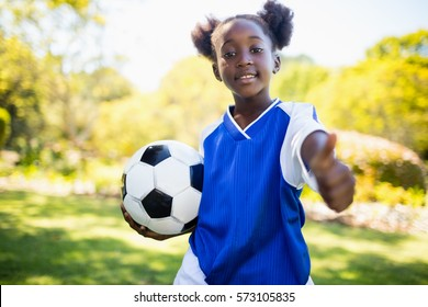 Portrait of girl with thumbs up in park