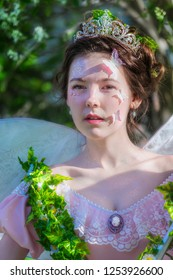 Portrait of a girl with a tiara on her head in the image of a fairy on a summer day against the background of green foliage.