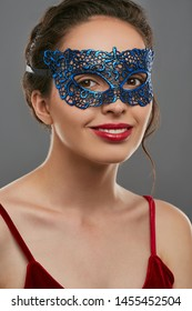 Portrait of girl with tied back brunette hair, wearing wine red crop top. The lady with slight smile is looking at camera, wearing blue carnival mask with perforation. Vintage carnival accessory.
