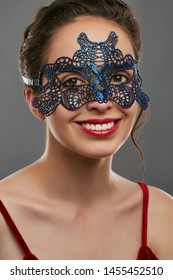 Portrait of girl with tied back dark hair, wearing red crop top. The smiling lady is looking at camera, wearing blue opalescent carnival mask with perforation. Vintage women's carnival accessory.