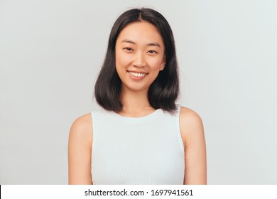 Portrait of girl tilts head and smiles sweetly showing white teeth. Beautiful young woman Asian appearance with black hair brown eyes stands isolated white background in Studio