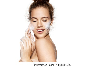 Portrait of girl touching flawless soft skin on white background. Woman using foam for wetting face. Pampering and freshness concept.