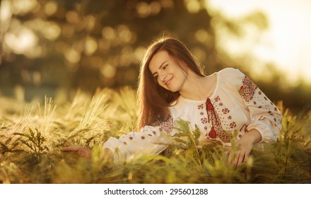 Portrait of the girl in the Ukrainian national clothes in wheat field