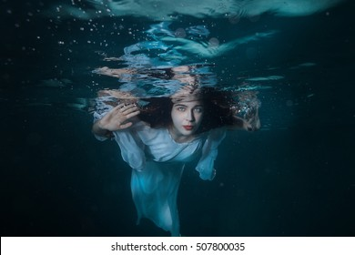 Portrait of a girl under the water, she is wearing a white dress.