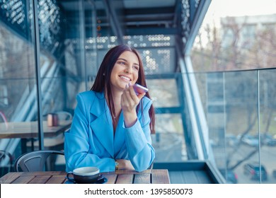 Portrait of a girl using the voice recognition of the phone sitting in a trendy cosy coffee shop cafe in Manhattan New York. Closeup portrait of a beautiful woman hispanic wearing formal blue suit.