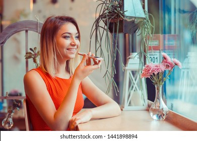 Portrait of a girl using the voice recognition of the phone sitting in her home kitchen, near window or  in a trendy cosy coffee shop cafe in Manhattan New York wearing red dress with white polka dots