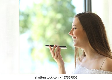 Portrait of a girl using the voice recognition of the phone and looking through a window of a house