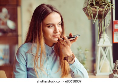 Portrait of a girl using the voice recognition of the phone sitting in a trendy cosy coffee shop cafe in Manhattan New York