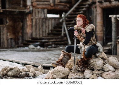 portrait of a girl in a Viking outfit, red hair. In the hands of the sword to fight the enemy