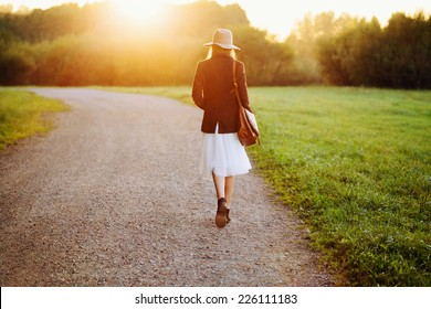 Portrait of girl walking down the road among fields in sunset light. Back to camera. Outside.