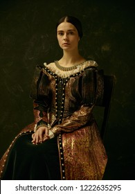 Portrait of a girl wearing a  antic   princess or countess dress over dark studio