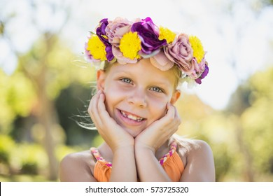 Portrait of girl wearing flower wreath smiling in park