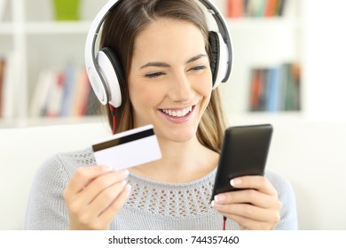 Portrait of a girl wearing headphones paying music on line with credit card and smart phone sitting on a sofa at home