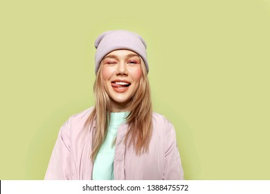 Portrait of ?ute girl wearing pink casual cap and stylish jacket. Beautiful model having fun and showing tongue. Green background. Copy space in right side