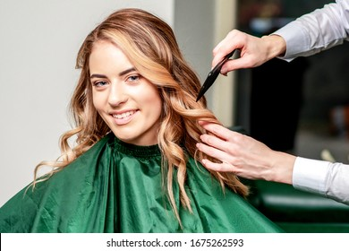 Portrait of girl while combing her hair by hairdresser in the salon.