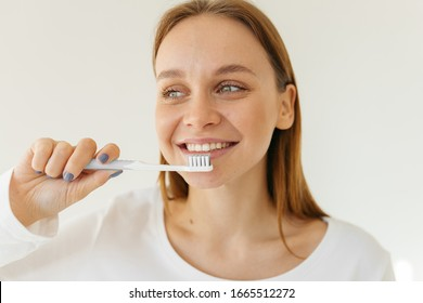 Portrait of a girl in a white blouse. Blonde with beautiful teeth laughs. Woman holds a toothbrush in her hand.