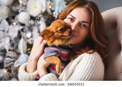 Portrait of a girl in white clothes with a little dog together over light christmas background