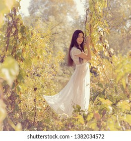Portrait of a girl in a white dress on nature