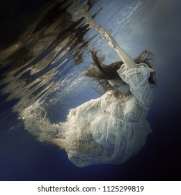 Portrait of a girl in a white dress under the water