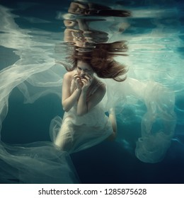 Portrait of a girl in a white dress under water