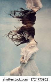 Portrait of a girl in a white dress underwater