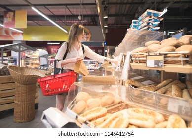 Portrait of a girl who buys a bun at the supermarket's bread department. A stylish woman with a red basket for products in her hands chooses bread in a supermarket. Buying products at the store