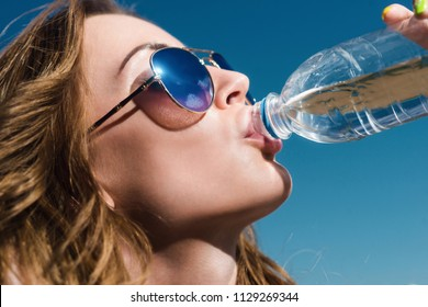 Portrait of a girl who drinks water from a bottle in summer
