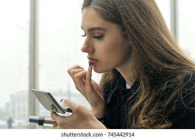 Portrait of a girl who paints her lips, holding in her hand a small mirror and lipstick. She has long brown hair and is dressed in a black coat. The brunette sits near the window in a public building.
