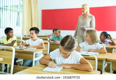 Portrait of girl who is posing at the desk in the classroom elementary school
