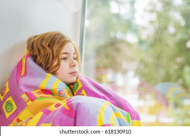 Portrait of a girl at the window wrapped in a blanket