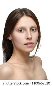 Portrait of a girl without make up looking at camera. model having beatiful face with nice smile, plump lips, big eyes and white teeth. Dark brown hair, opened shoulders. White studio background.